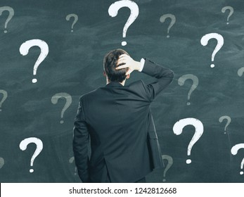 Back view of young businessman on chalkboard wall background with question marks. Confusion and complexity concept