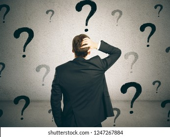 Back view of young businessman on concrete wall background with question marks. Confusion and doubt concept