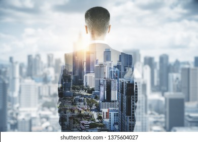 Back view of young businessman on blurry bright city background. Research and vision concept. Double exposure