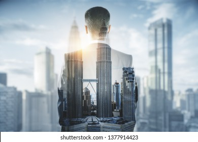 Back view of young businessman on blurry bright city background. Research and success concept. Double exposure