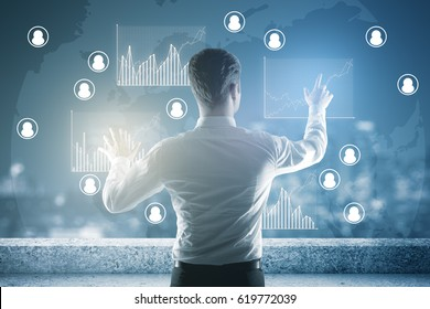 Back view of young businessman on rooftop managing business charts. Human resources concept
