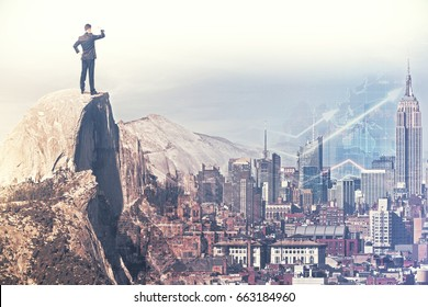 Back view of young businessman on mountain top looking into the distance. City background with forex chart. Prosperity concept