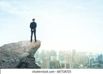 Back view of young businessman on mountain top looking at city with daylight. Future concept. Copy space