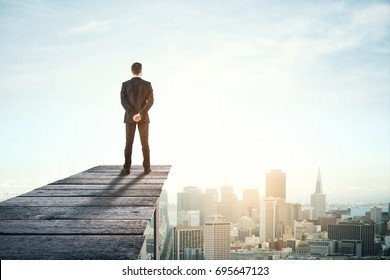 Back view of young businessman on wooden pier looking at city with copy space. Research concept