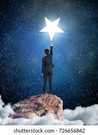 Back view of young businessman on cloudy mountain top reaching bright star. Aim concept