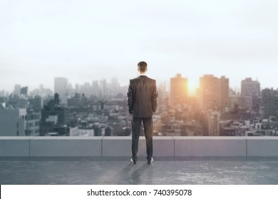 Back view of young businessman on rooftop looking into the distance on city background with sunlight. Research concept