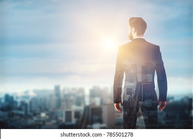 Back view of young businessman on blurry city background with sunlight and copy space. Double exposure
