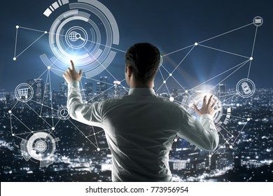 Back view of young businessman pointing at abstract digital business hologram on city background. Infograph and finance concept. Double exposure
