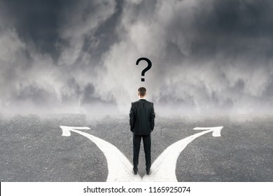 Back view of young businessman with question mark and two arrows on concrete road. Cloudy sky background. Different direction and confusion concept