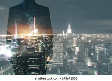 Back view of young businessman silhouette standing on creative night city background with copy space. Employment concept. Double exposure
