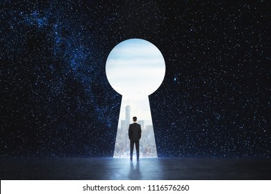 Back view of young businessman standing against keyhole door on starry sky background. Dream, success, opportunity and startup concept