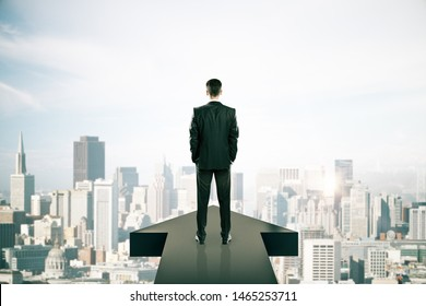 Back view of young businessman standing on arrow on New York city background. Growth and development concept