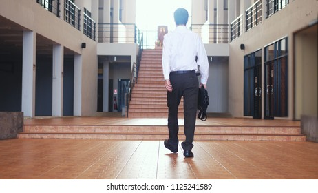 Back of view of young businessman in a suit walks with a briefcase in a business centre.