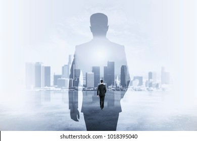 Back view of young businessman walking on abstract city background. Success and employment concept. Double exposure