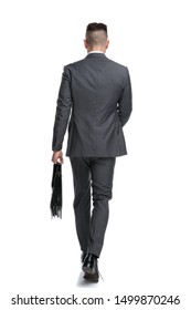 back view of a young businessman walking forward isolated on white background