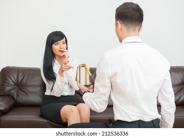Back view of young businessman wearing official costume giving a white gift box to his beautiful colleague women and standing on his knees in office interior
