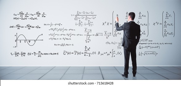 Back view of young businessman writing mathematical formulas on concrete wall in interior. Science concept