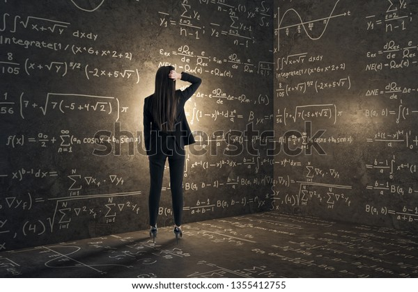 Back view of young businesswoman in concrete corner with mathematical formulas. Complex algorithm and math concept