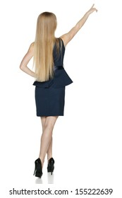 Back view of young businesswoman in full length pointing at blank copy space, isolated on white