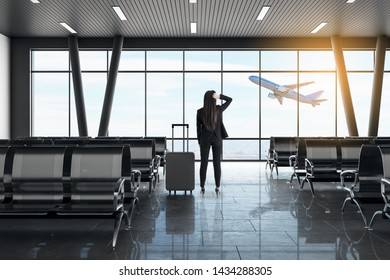 Back view of young businesswoman looking out of window in modern airport lounge interior with daylight, suitcase and airplane. Travel and vacation concept.