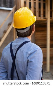 Back view of young carpenter with yellow hard hat and blue shirt outdoor, wooden background