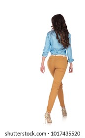back view of a young casual woman walking on white background