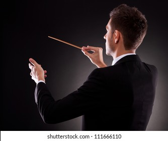 Back view of a young composer directing with his baton, on black background
