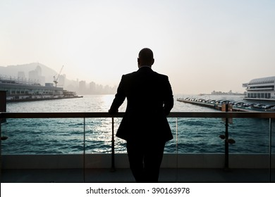 Back view of a young confident man financier is thinking about something, while is standing outdoors against sea port. Silhouette of male intelligent managing director is resting after hard work day