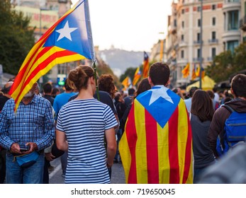 Back view of young couple carrying and independence flag in a demonstration in Barcelona