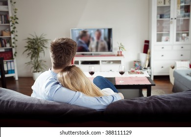 Back view of young couple enjoying themselves and watching tv on the sofa in the living room. Young man and woman relaxing and drinking red wine in the new flat. Man is hugging his girlfriend.