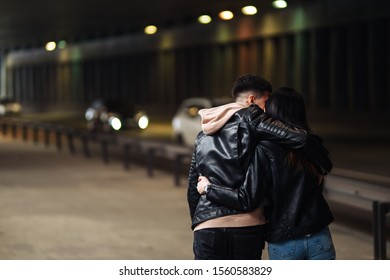 Back view of young couple  holding hand going through a dark tunnel. Stylish couple in love hug each other on the black background with lights. Together. Love, romantic, tenderness concept.