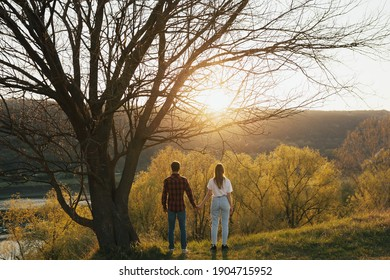 Back view of young couple holding hands and watching beautiful sunset and landscape.