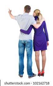 Back view young couple pointing at wall (woman and man). guy in jeans and  girl in blue dress. Rear view people collection.  backside view of person.  Isolated over white background