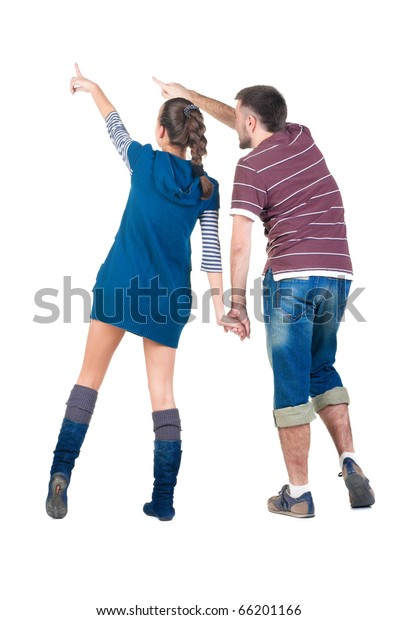 Back view of young couple pointing at white wall . Rear view .