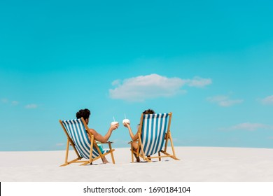 back view of young couple sitting in deck chairs with coconut drinks on sandy beach
