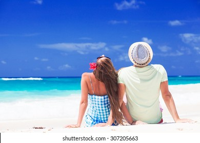 Back view of young couple sitting by the sea. remote tropical beaches and countries. travel concept
