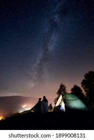 Back view of young couple tourists having a rest at bonfire near illuminated tent under amazing night sky full of stars and Milky way. On background beautiful starry sky, mountains and luminous city