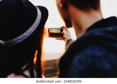 Back view of young couple using smartphone to take photo of magnificent sundown in nature.Unrecognizable couple taking picture of sundown