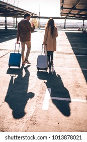 Back view of young couple walking with suitcases on parking lot in airport.