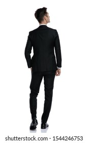 back view of young elegant man in tuxedo looking up and thinking, walking isolated on white background, full body