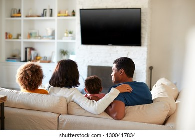 Back view of young family sitting on the sofa and watching TV together in their living room, close up