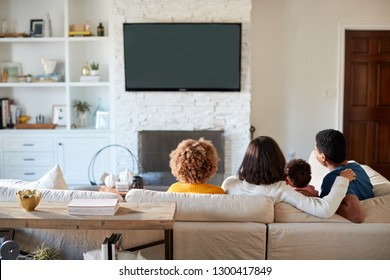Back view of young family sitting on the sofa and watching TV together in their living room