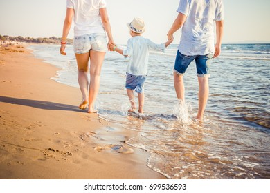 Back view of young family walking on beach at sunset