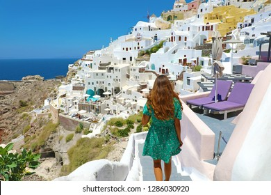 Back view of young fashion woman with green dress walking on stairs in Oia, Santorini. Female travel tourist on her summer vacations in Greece.