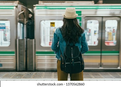 back view of young female backpacker stand on platform waiting subway train in underground station. Public transport people travel commute city urban concept. woman tourist watch metro drive leaving.