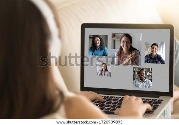 Back view of young female sit rest on sofa ta home talk chat online on video call on laptop with diverse friends, millennial girl have webcam conference on computer with multiracial pals or colleagues