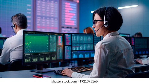 Back view of young female trader with headset speaking and browsing data on computer while working in office of stock exchange company