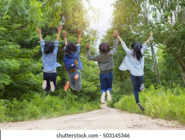 Back view of young friends jumping for joy. To travel during the holidays.