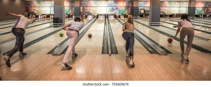 Back view of young friends throwing the balls while playing bowling together