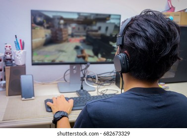 Back view of young gamer playing FPS video games at home